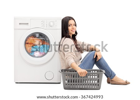Young woman waiting for the laundry seated by a washing machine isolated on white background - stock photo