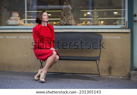 Young woman waiting her friend on metal bench - stock photo