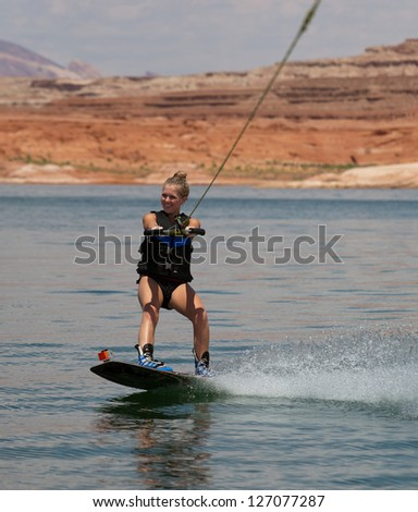 Young woman wakeboarding at Lake Powell in the southwestern US desert. - stock photo