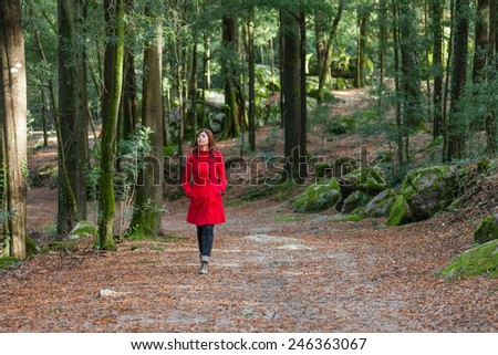Young woman walking alone on a forest path wearing a red overcoat - stock photo