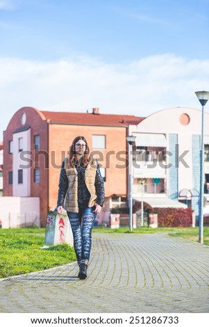 Young Woman Walking at Park in the Morning. The Girl is Looking Ahead. The Park is in a Residential Area, there are some Houses on Background. - stock photo
