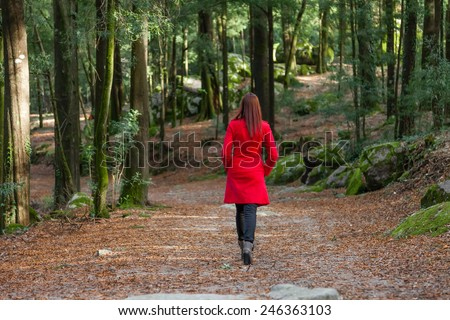 Young woman walking away alone on a forest path wearing a red overcoat - stock photo