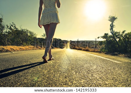 young woman walking barefoot on a long deserted road - stock photo
