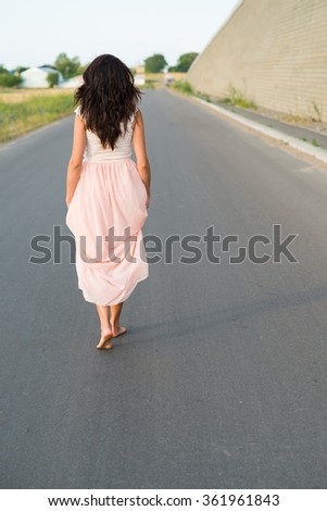 young woman walking barefoot on the road - stock photo