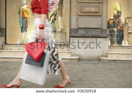 Young woman walking by a shop window, with shopping bags. - stock photo