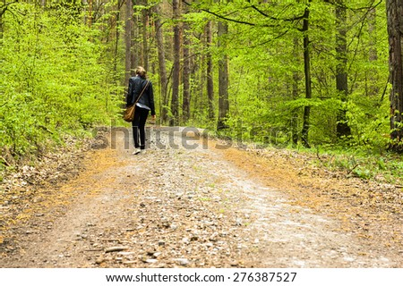 Young woman walking in the spring forest  - stock photo