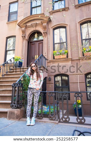 Young woman walking near old houses in historic district of West Village - stock photo