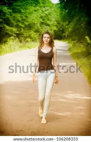 Young woman walking on a countryside road in summertime. - stock photo