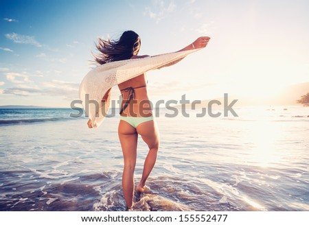 Young woman walking on a sandy beach at Sunset, Dreamy Lighting - stock photo