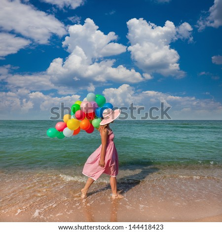 Young woman walking on the beach with colored balloons / Summer relaxations - stock photo