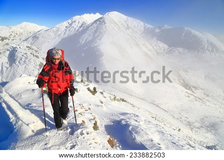 Young woman walking on the mountain on snow covered trail - stock photo