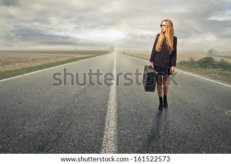 young woman walking on the road with a suitcase - stock photo