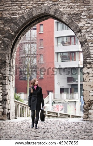 Young woman walking on the streets of old european city - stock photo