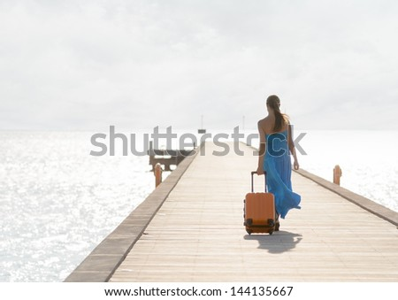 Young woman walking on wooden pier. - stock photo