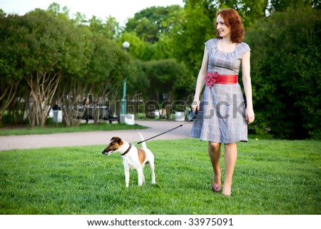 young woman walking with her dog in a park - stock photo
