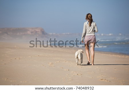 Young woman walking with her dog on the beach - stock photo