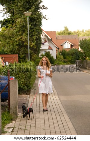 Young woman walking with her two small dogs. - stock photo