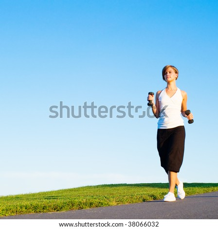 Young woman walking with weights, from a complete series of photos. - stock photo
