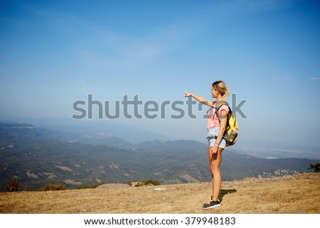 Young woman wanderer points finger on copy space while standing on a mountain hill against amazing view, female traveler enjoying beautiful landscape while taking break during hiking in summer day - stock photo