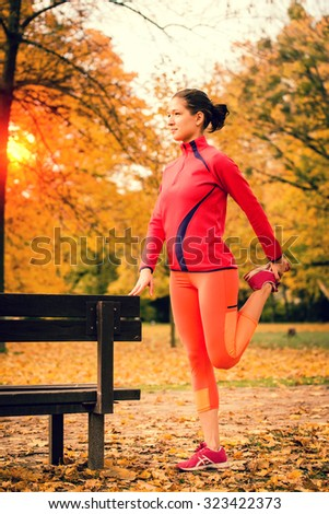 Young woman warming up at bench before jogging in autumn nature - stock photo