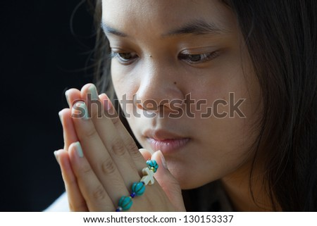 Young woman was holding blue rosary in hands - stock photo