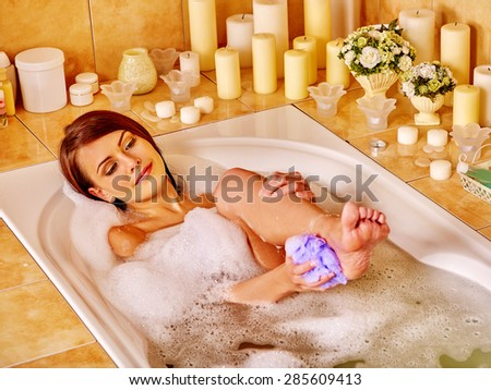 Young woman wash leg and heel in bathtube. - stock photo