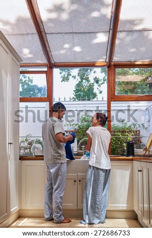 young woman washing dirty dishes together in kitchen - stock photo