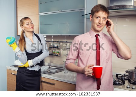 Young woman washing dishes and her boyfriend talking by mobile phone in kitchen - stock photo