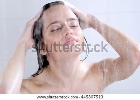 Young woman washing head with shampoo - stock photo