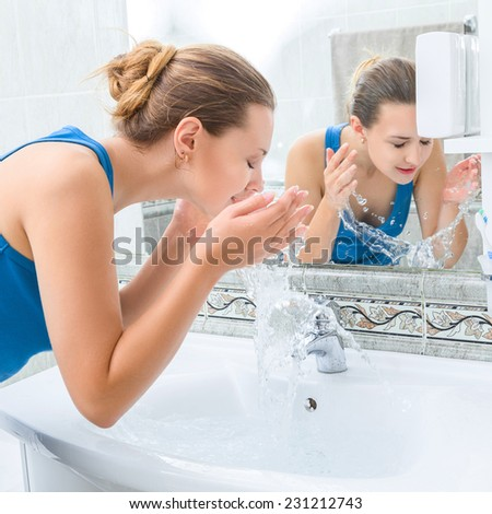 Young woman washing her face with clean water in bathroom - stock photo