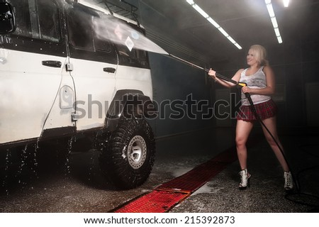 Young woman washing offroad car by water hose - stock photo