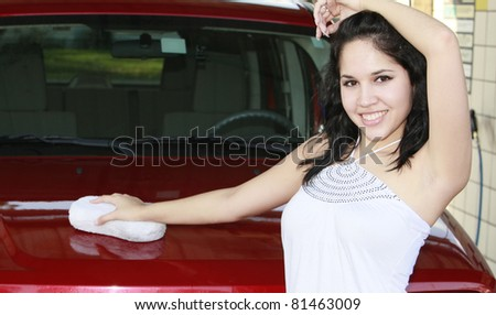 young woman washing red car with sponge - stock photo