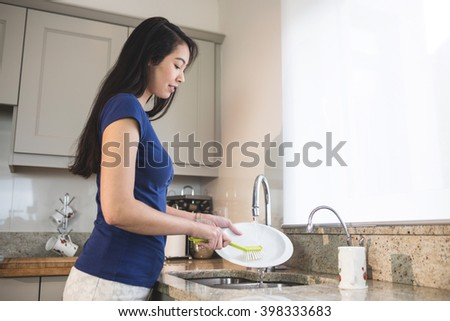 Young woman washing up in the kitchen at home - stock photo