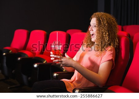 Young woman watching a film at the cinema - stock photo