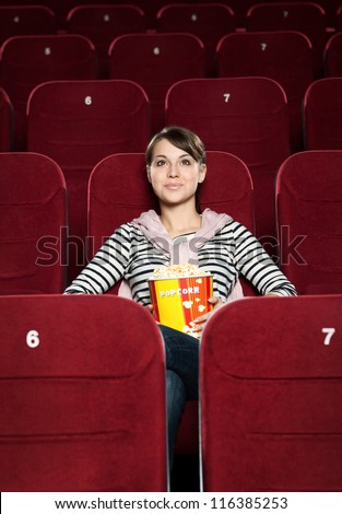 Young woman watching a movie alone at the cinema - stock photo