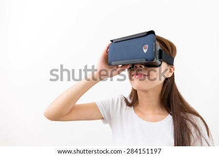Young woman watching though the VR device - stock photo