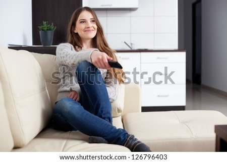 Young woman watching TV on sofa - stock photo