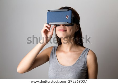 Young Woman watching via the VR device - stock photo