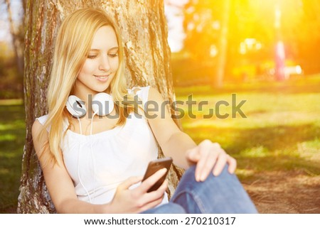 Young woman watching video stream with smartphone in a park in summer - stock photo