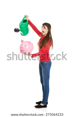 Young woman waters piggybank with watering can. - stock photo