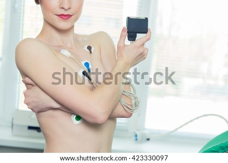 Young woman wearing a Holter Heart Monitor. - stock photo