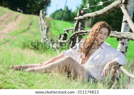 Young woman wearing a shirt over naked body enjoying the sun, sitting near the rural road - stock photo