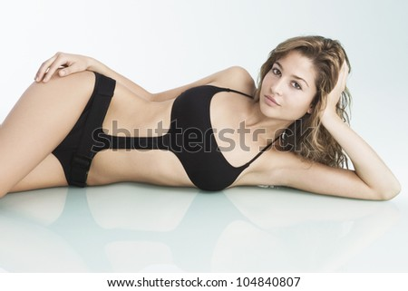 Young woman wearing a swimming costume and laying down on a reflective glass surface. - stock photo