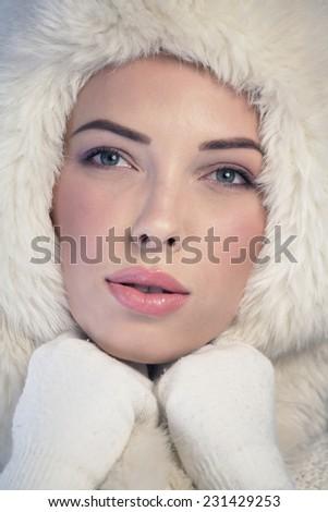 Young woman wearing a white fur cap - stock photo