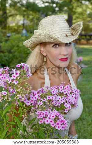 Young woman wearing cowgirl hat and posing behind beautiful pink flowers in garden - stock photo