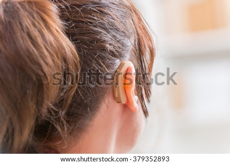 Young woman wearing deaf aid - stock photo