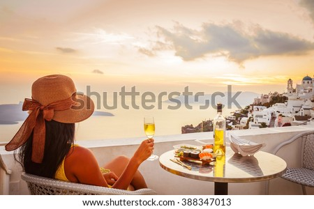 Young woman wearing hat, looking at beautiful view of Caldera and enjoying romantic dinner during sunset before getting dark over Aegean sea, Santorini - stock photo