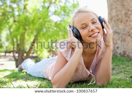 Young woman wearing headphones while lying on the lawn - stock photo