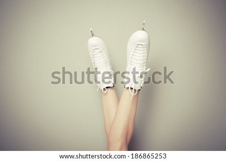Young woman wearing ice skates with her legs up against a wall - stock photo
