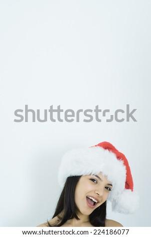 Young woman wearing santa hat, portrait - stock photo